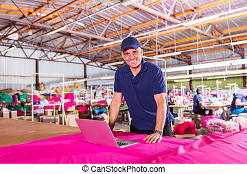 senior clothing factory manager with laptop computer