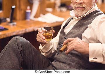 Senior confident owner enjoying free time in his salon