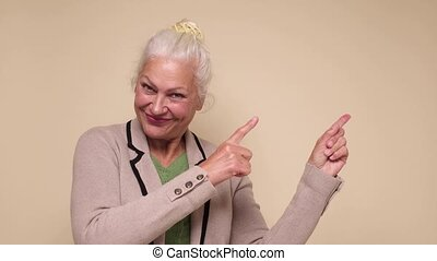 Senior confident woman pointing aside on copyspace. Studio shot