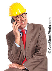 senior construcion engineer talking on the phone and looks ...