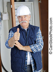 senior construction worker looking at plans on job