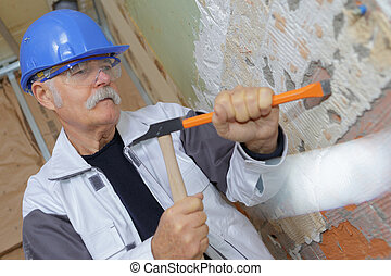 senior construction worker with a chisel and hammer