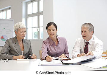 Three people in a business meeting working togehter
