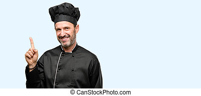 Senior cook man, wearing chef hat pointing away side with finger