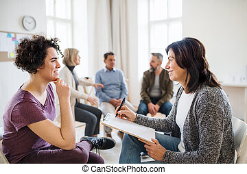 Senior counsellor with clipboard talking to a woman during group therapy.