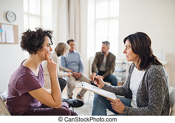 Senior counselor with clipboard talking to a woman during group therapy.