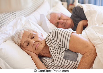 Senior couple asleep in their bed at home