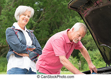 Senior couple at broken car
