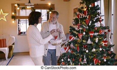 Senior couple at home decorating Christmas tree. - Beautiful...
