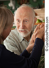Senior couple at home holding hands focusing on man