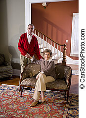 Senior couple at home in living room