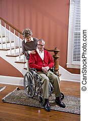 Senior couple at home, man in wheelchair