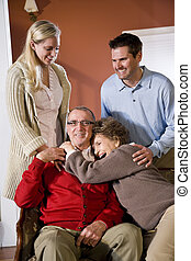 Senior couple at home on sofa with adult children