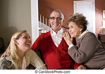 Senior couple at home with adult daughter