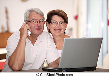 Senior couple at home with laptop computer