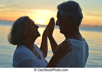 Senior couple at sea at sunset