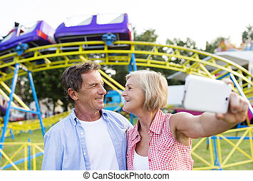 Senior couple at the fun fair - Senior couple having a good...
