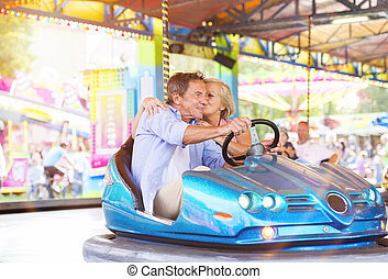Senior couple at the fun fair - Senior couple having a ride...