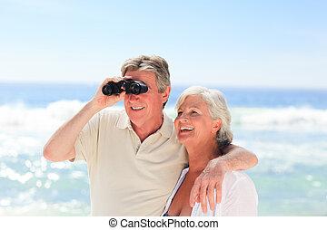 Senior couple bird watching at the beach