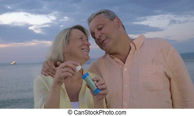 Senior couple blowing bubbles at the seaside