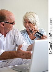 Senior couple booking a holiday on-line