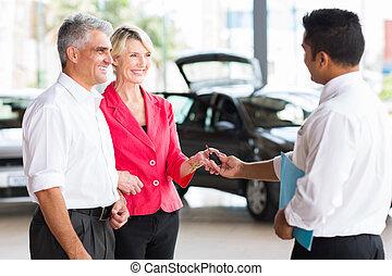 senior couple buying a new car