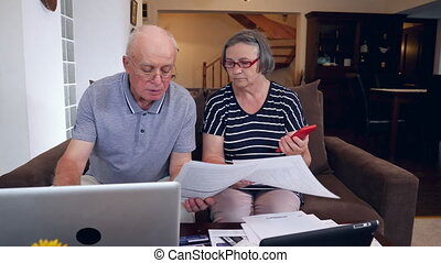 Senior couple calculating bills cost at home - Nervous...