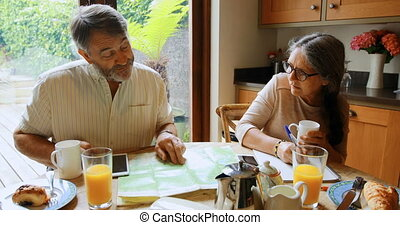 Senior couple calculating invoices at home 4k