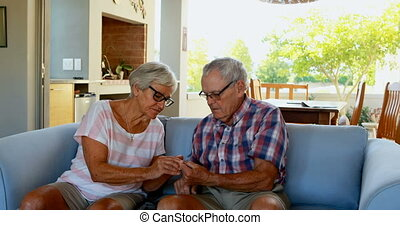 Senior couple checking blood sugar on glucometer 4k - Senior...