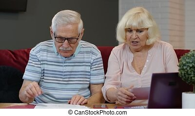 Senior couple checking papers, domestic bills, planning ...