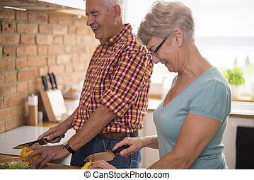 Senior couple colaborating in the kitchen