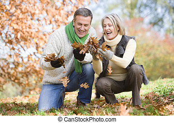 Senior couple collecting autumn leaves