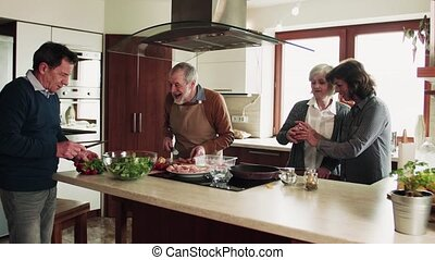 Senior couple cooking dinner together with friends at home.