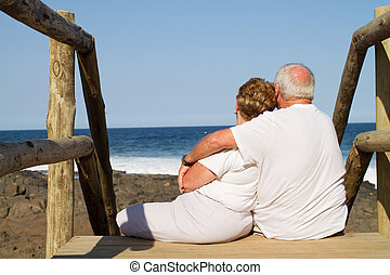 senior couple cuddling on beach stairs