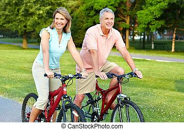 senior couple cycling - Happy elderly senior couple cycling...