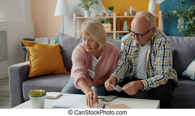 Senior couple dealing with financial papers and counting ...