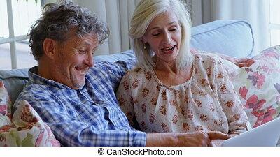 Senior couple discussing over laptop on sofa 4k - Senior...