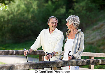 Senior couple doing a Nordic walk on bridge - Happy senior...