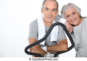 senior couple doing exercises in the gym