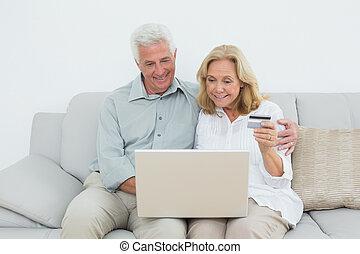 Senior couple doing online shopping on sofa