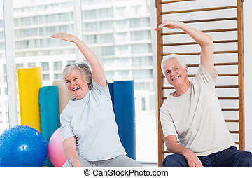 Senior couple doing stretching exercise in gym