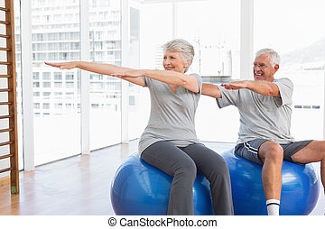 Happy senior couple doing stretching exercises on fitness balls in the medical office