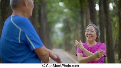 Senior Couple doing stretching on the forest road