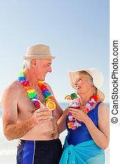 Senior couple drinking a cocktail on the beach