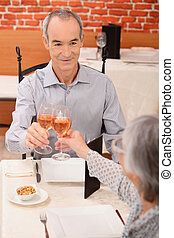 Senior couple drinking rose in a restaurant