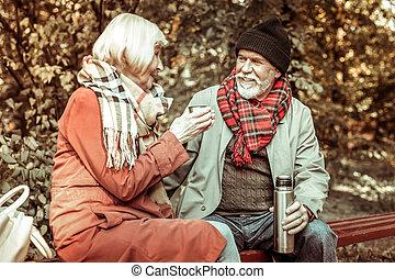 Senior couple drinking tea in the park.