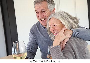 Senior couple drinking wine in home kitchen