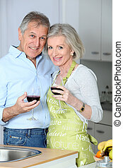 Senior couple drinking wine in kitchen
