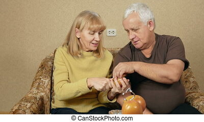 Senior couple eating fruit at home on the couch. Woman cuts off a piece of persimmon and gives men overweight. Healthy food concept