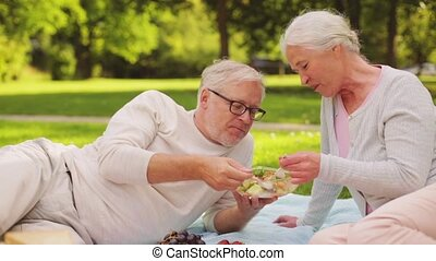 senior couple eating salad at picnic in park - old age,...